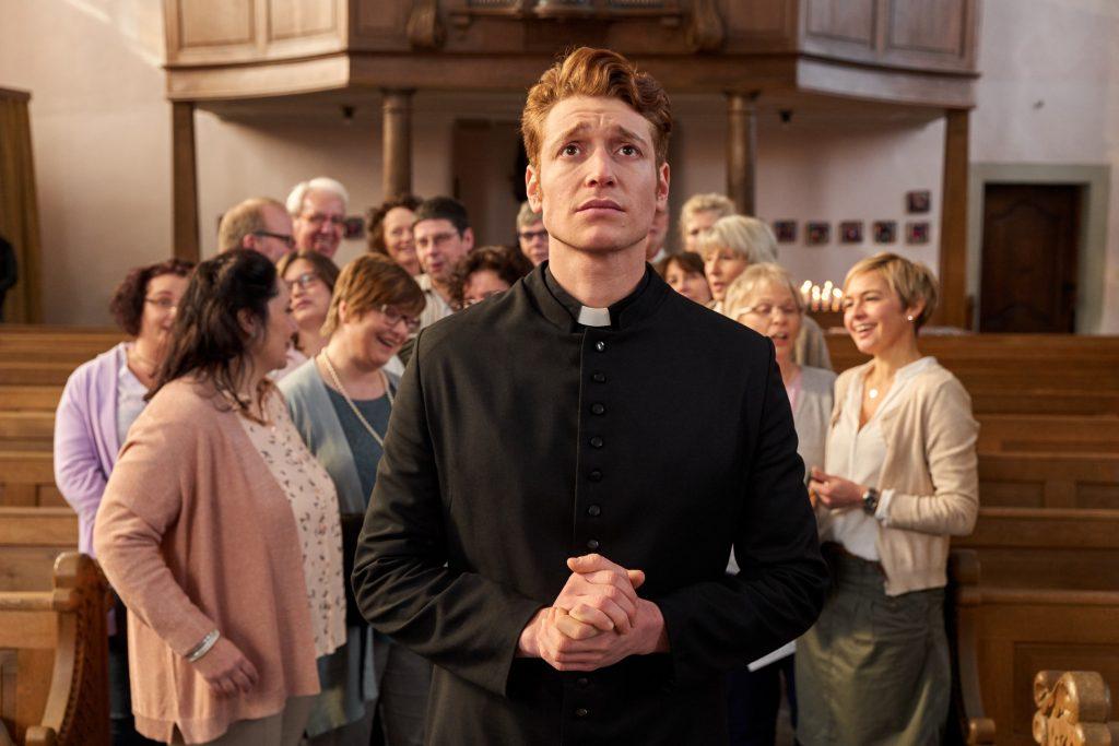 Maik (Daniel Donskoy) wird überschwenglich vom Kirchen-Chor begrüßt. Ihn beschleicht ein mulmiges Gefühl.